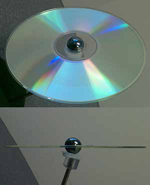 A photo of a CD seen top down with a marble stuck in the center; A photo of the same CD disk and marble seen edge on
