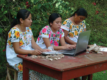 Maya women at San Simon enter GIS data into a computer to tag pottery sherds. Image Credit: Jose Huchim Herrera, INAH