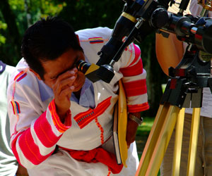 Maya man observes the Sun through a special telescope.