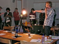 adults standing in a circle around a lit light bulb