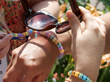 hands holding sunglasses and wearing colorful beads