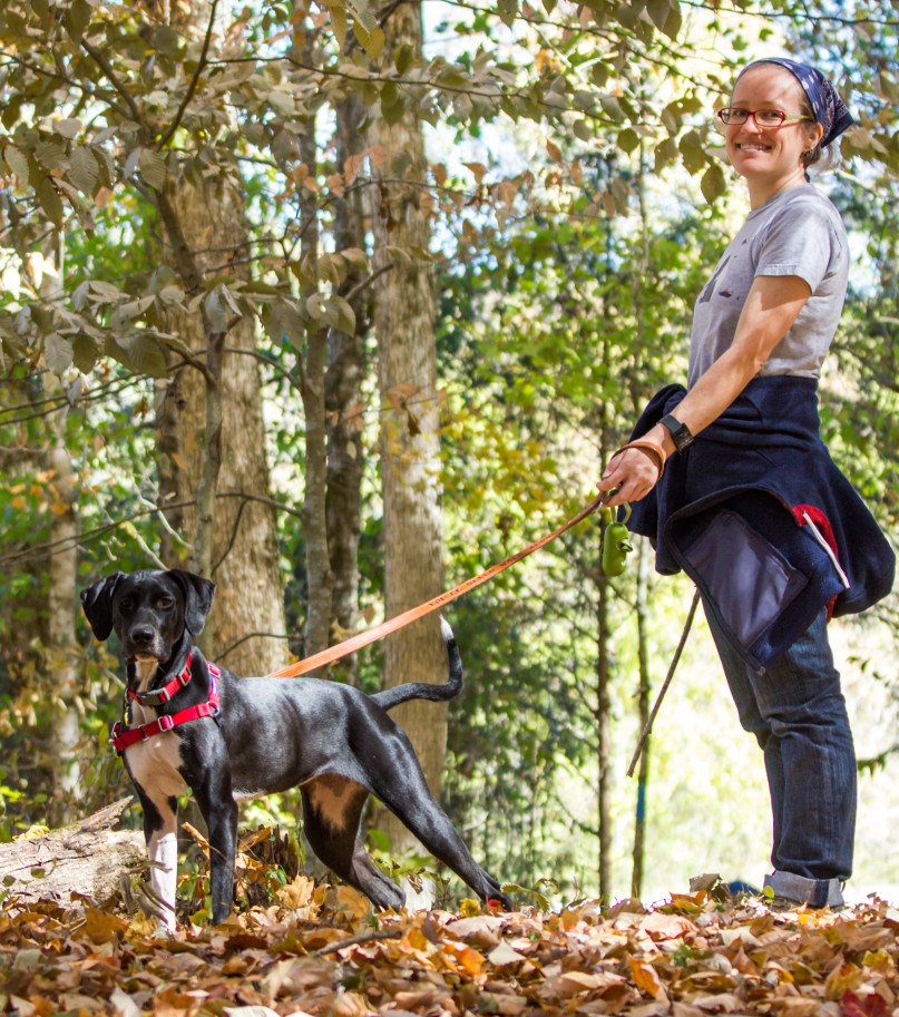 smiling woman with dog in woods